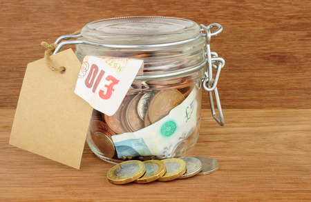 stash: Glass jar filled with cash savings on a wood background
