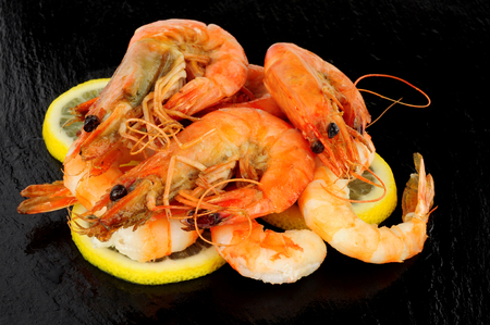 Group of whole fried king tiger prawns on a slate stone background