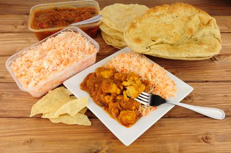 Indiase curry om mee te nemen maaltijd met poppadoms en nan brood Stockfoto