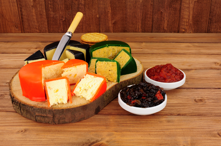stilton: Group of English wax covered cheeses on a wooden background Stock Photo