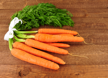 Fresh raw carrots with tops on a rustic wood background