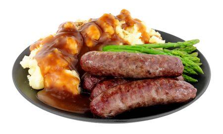 으깬 된 감자와 아스파라거스 흰색 배경에 고립 된 검정 잉크 판에 튀긴 된 사슴 고기 소시지 식사