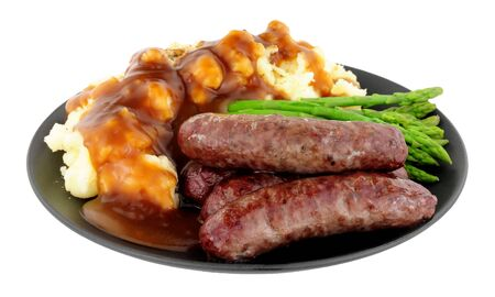 Fried venison sausages meal with mashed potatoes and asparagus on a black plate isolated on a white background