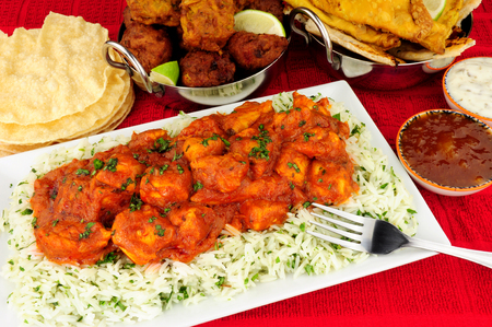 Chicken curry meal with rice and a selection of sides and dips