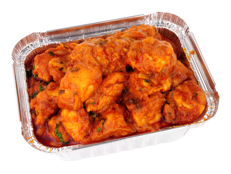 Spicy chicken curry take away in a foil container isolated on a white background