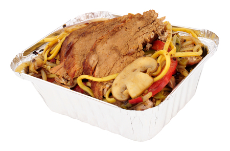 Chinese pork chow mein take away meal in an aluminium tray isolated on a white background