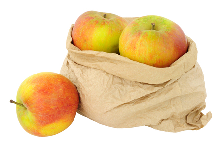 Fresh apples in an environmentally friendly brown paper bag isolated on a white background