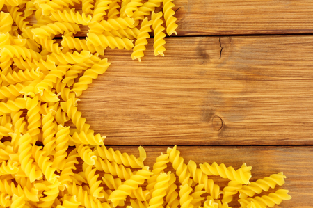 Uncooked Eliche pasta on a wood background