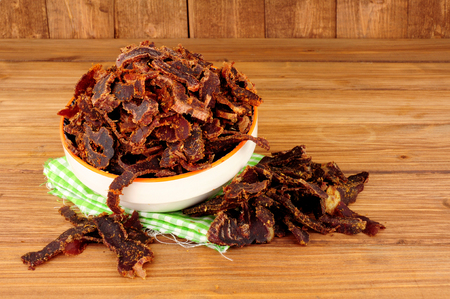 Bowl of shredded biltong meat on a wooden background