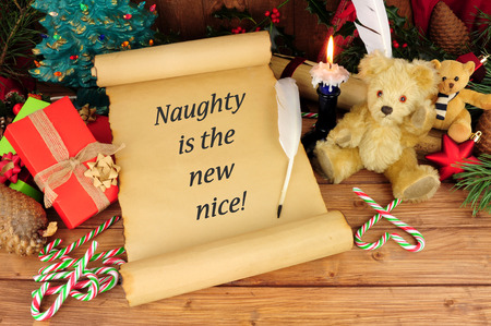 Old paper scroll with a humorous Christmas slogan, naughty is the new nice text