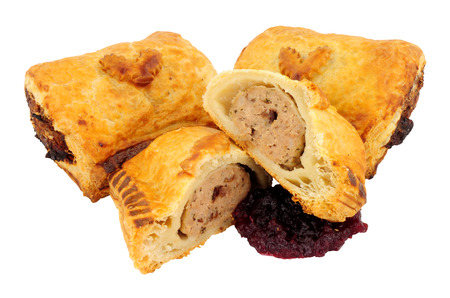 Turkey and cranberry sausage rolls with Christmas holly leaf decoration isolated on a white background Stock Photo