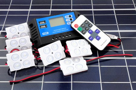 Solar lighting kit with lights and charger control unit and remote control on a solar panel background