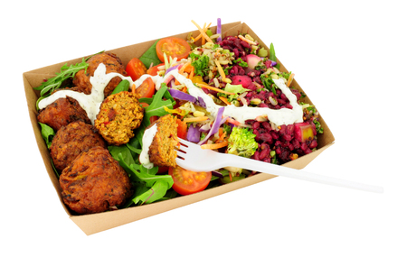 Veggie Buddha salad with falafel in a cardboard take away box isolated on a white background