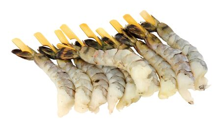 Groupe de crevettes tigrées noires crues fraîches sur des brochettes en bois isolées sur fond blanc