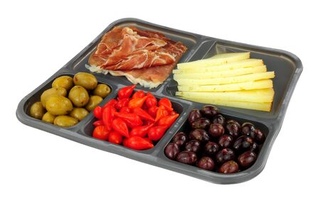Tray of supermarket Spanish tapas with Serrano ham, Queen green olives, sweet flame peppers and Manchego cheese isolated on a white background