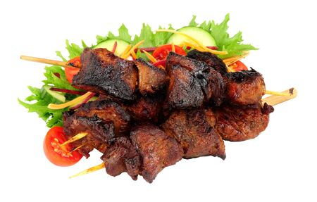 Barbecued burnt ends beef kebabs on wooden skewers with fresh salad isolated on a white background Фото со стока