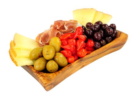 Assortment of Spanish tapas with Serrano ham, Queen green olives, sweet flame peppers and Manchego cheese in an olive wood bowl isolated on a white background