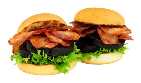 Fried bacon and black pudding sandwich rolls with lettuce isolated on a white background