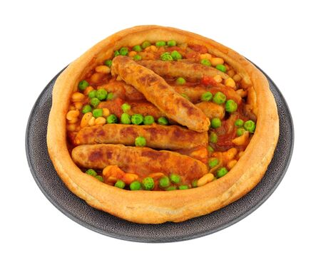Sausage and bean casserole served in a large Yorkshire pudding isolated on a white background Stock Photo