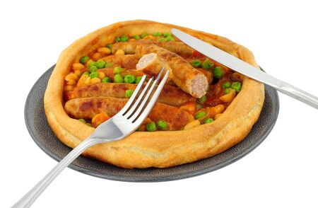 Sausage and bean casserole served in a large Yorkshire pudding isolated on a white background Reklamní fotografie