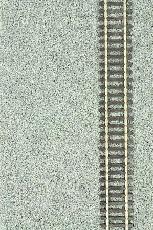 Fine grey gravel background used as track ballast for model railways with section of track