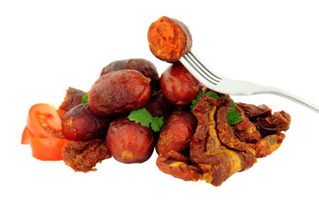 Group of spicy chorizo meatballs with sun dried and fresh tomatoes isolated on a white background