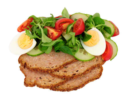Thin slices of haslet meat with a fresh egg salad meal isolated on a white background, haslet is an English pork and herb meatloaf also sometimes called acelet