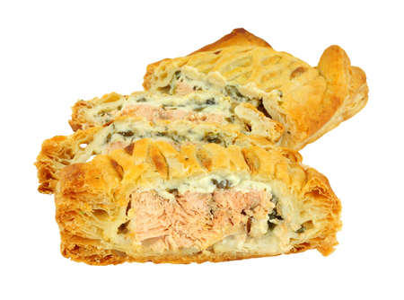 Sliced puff pastry covered salmon Wellington with cheese spinach filling isolated on a white background 免版税图像