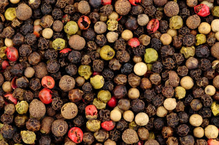 Mixed whole peppercorn background including, black, white, green and pimento berries