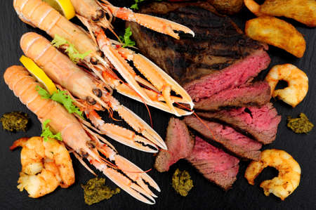 Surf and turf meal with sirloin steak, langoustine and tiger prawns on a slate background 写真素材