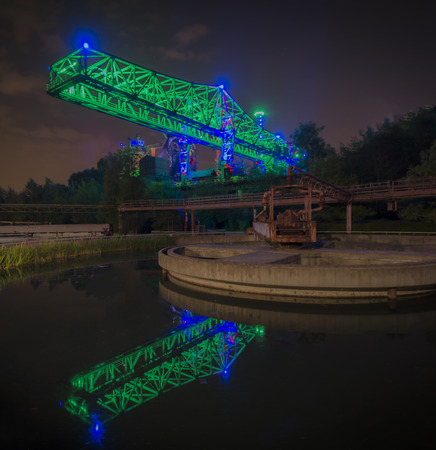 steel works: Old steel works in Duisburg, Germany with a crane reflecting in a cooling tower