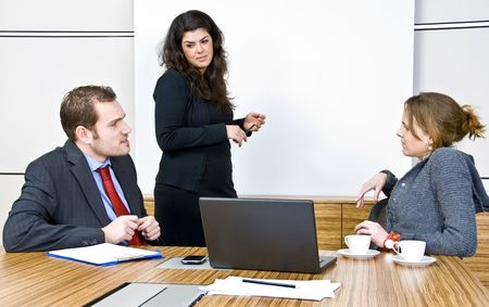 office scene: An office scene comprising of staff discussing business matters in front of a presentation screen