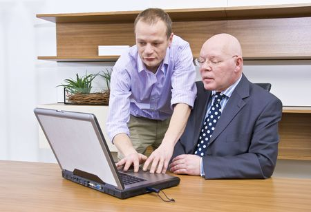 A company director being shown how to operate a laptop by a computer technician Stock Photo - 4214437