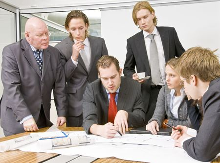 An office scene comprising of a manager discussing plans with his staff Stock Photo - 4214438