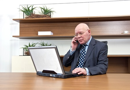 A company executive sitting at his desk, talking on his mobile telephone Stock Photo - 4251204