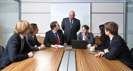 A company manager, and his team, discussing business strategies during an office meeting