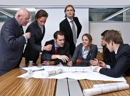 supervisi�n: Un director de la compa��a, y su equipo, discutir los planes en una oficina moderna