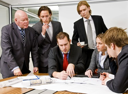 An office scene comprising of a manager discussing plans with his staff photo