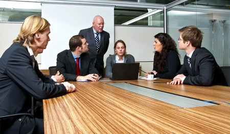 authoritative woman: A company manager, and his team, discussing matters during an office meeting
