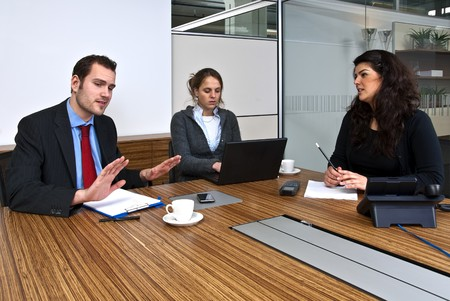 Three staff members discussing business matters in front of a presentation screen photo