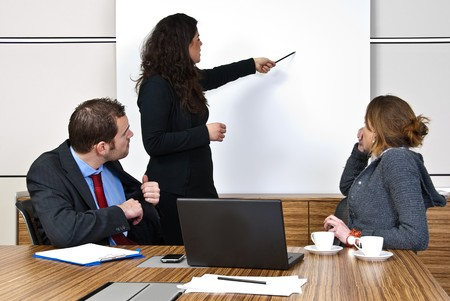 Two staff members paying attention to a team leader, pointing to items on a presentation screen Stock Photo - 4301658