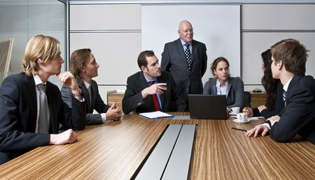 authoritative woman: An office meeting between a senior executive and six of his junior staff members