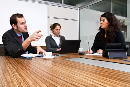 Three young staff members discussing business matters in a  modern office cubicle Stock Photo - 4336469