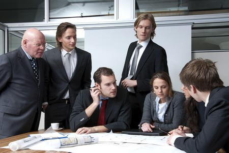 A company director discussing plans with his young staff members photo