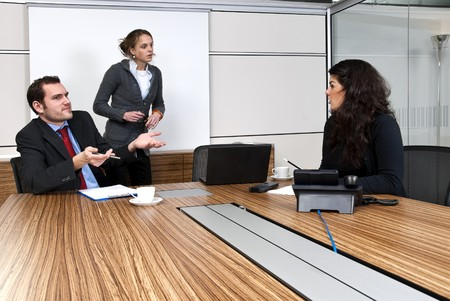 Three young staff members discussing business matters in a  modern office cubicle Stock Photo - 4374087