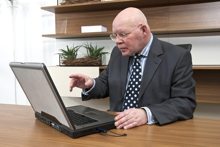A company director checking data on his laptop photo