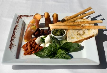 antipasto platter: An Antipasto platter containing Semi-dried Tomatoes, Baby Bocconcini, Prosciutto-wrapped Rockmelon, Black Olives, and Sour Dough