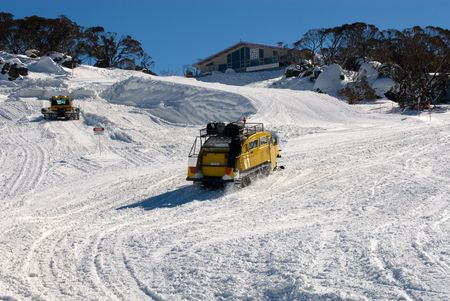 snow grooming machine: A snow grooming machine grooming the slopes, whilst a snow transport vehicle carring guests makes its way to a nearby chalet, Perisher Valley, Australia