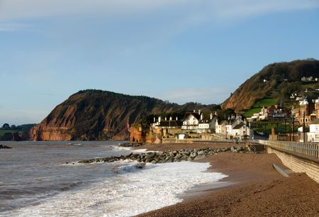 Thatched roofed houses beside the  beach and sea wall in Sidmouth, England photo