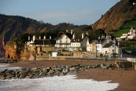 devon: Thatched roofed houses beside the  beach and sea wall in Sidmouth, England Stock Photo